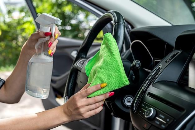 Mano con panno in microfibra verde per la pulizia della console interna dell'auto, primo piano
