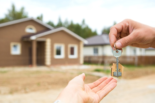 Mano con una chiave e una casa portachiavi in legno. costruire, progettare, trasferirsi in una nuova casa, mutuo, affittare e acquistare immobili. per aprire la porta. copia spazio