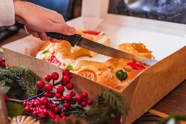 Mano con un coltello che taglia un dolce natalizio spagnolo tradizionale fatto con pasta, frutta e panna