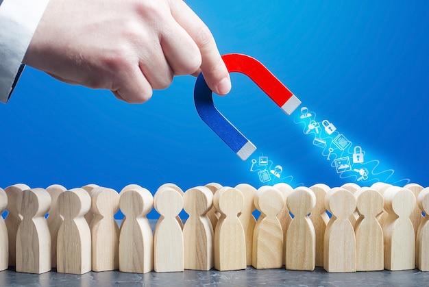 La mano con un magnete raccoglie i dati personali dagli utenti di internet in linea di figure della folla.