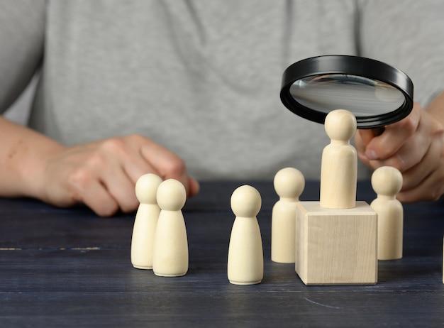 Una mano con una lente d'ingrandimento esamina uomini di legno unici e di talento tra la folla. concetto di ricerca dei dipendenti, crescita della carriera, licenziamenti e assunzioni