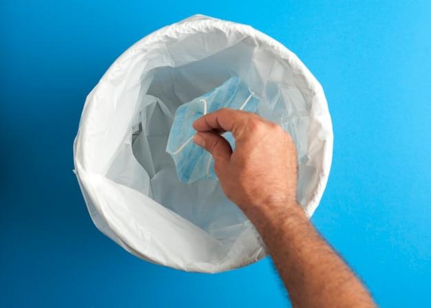 Mano con maschera, depositando nel cestino, sfondo blu