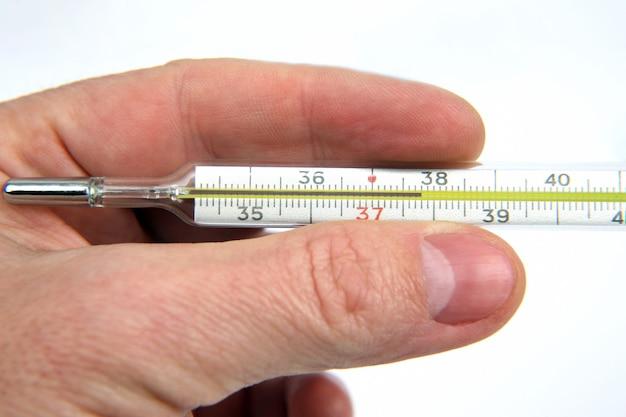 La mano con il termometro medico si chiuda