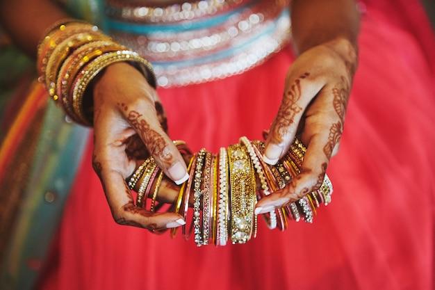 La mano con mehndi della sposa indiana che tiene un sacco di braccialetti glitterati
