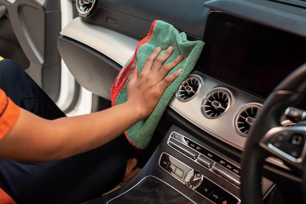 Mano con panno in microfibra per pulizia interni auto.