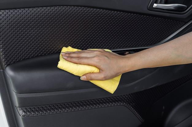 Mano con panno in microfibra per la pulizia della porta interna dell'auto