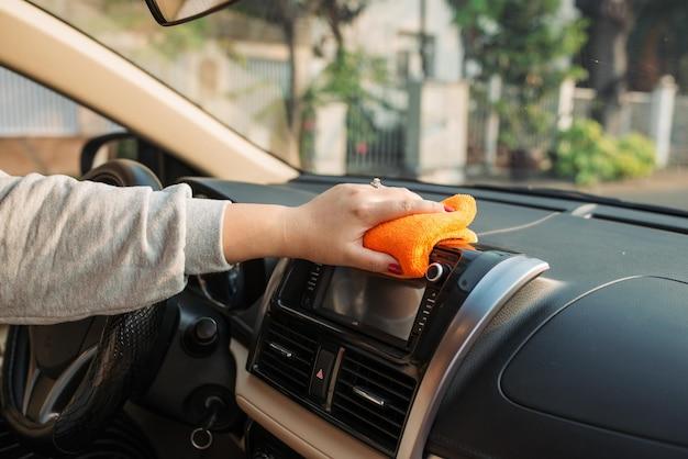 Mano con sedile per la pulizia del panno in microfibra, dettagli automatici e concetto di valeting, lavaggio degli interni per la cura dell'auto, messa a fuoco selettiva