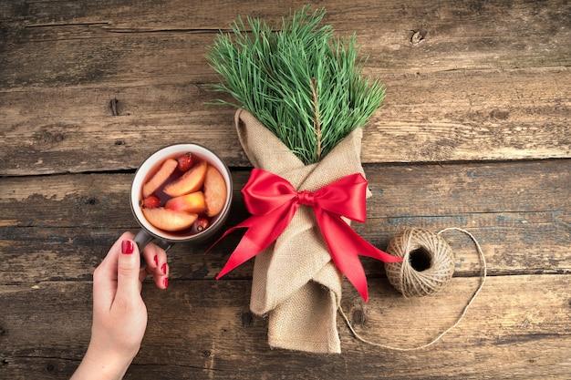 Mano con una tazza di vin brulè e un bouquet di rami di pino con un fiocco rosso.
