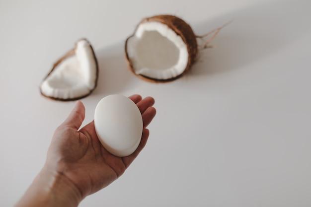 Mano con un sapone di cocco naturale o una barra di shampoo su sfondo bianco