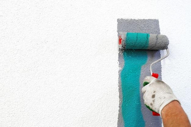 Mano con rullo di vernice in mano, dipingendo un muro