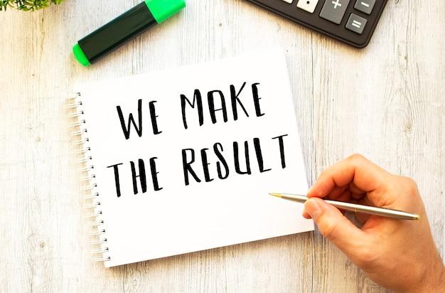 Una mano con una penna scrive il testo facciamo il risultato in un taccuino su una scrivania di legno. vista dall'alto. concetto di affari.