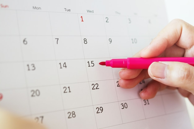 Mano con scrittura a penna sulla data del calendario