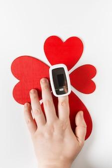 Mano con pulsossimetro su un dito e un simbolo del cuore