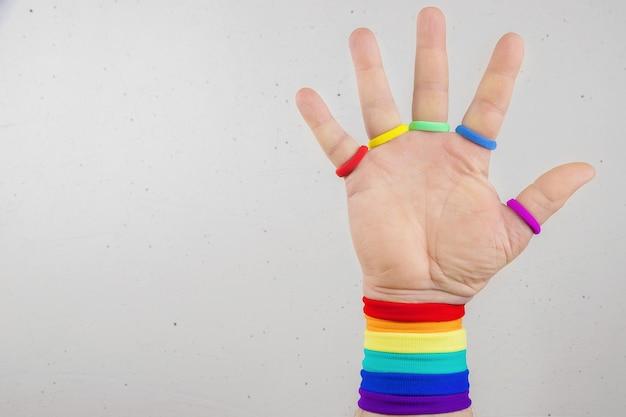 Mano con bracciali color arcobaleno tema lgbt