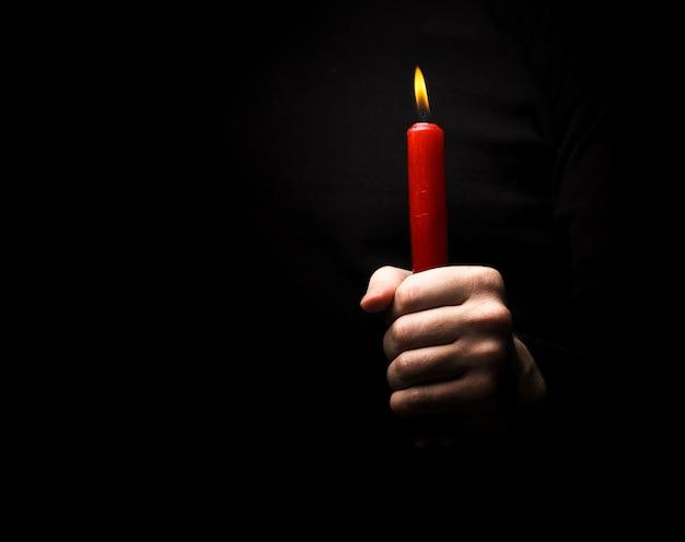Mano con una candela rossa
