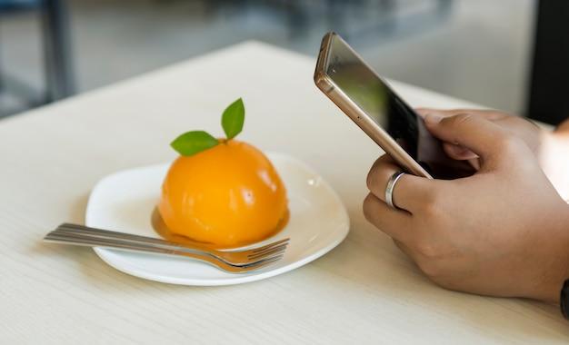 La mano con lo smartphone prende la foto alla torta arancio della frutta in piatto bianco