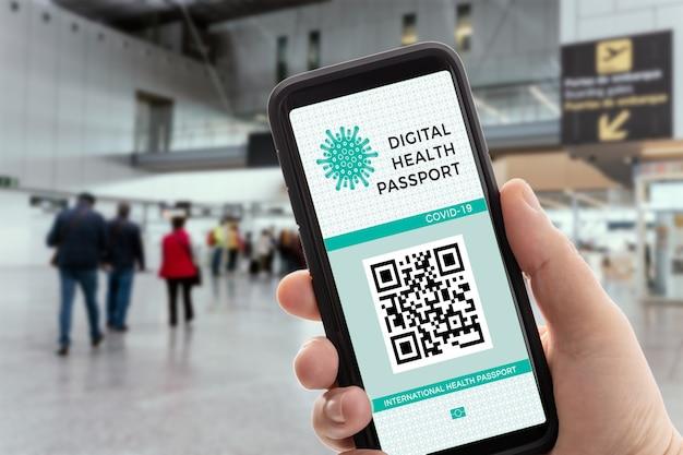 Mano con uno smartphone con la salute digitale o il passaporto per le vaccinazioni sullo schermo.