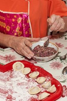 Una mano con un cucchiaio mescola la carne macinata per fare gli gnocchi. colpo verticale