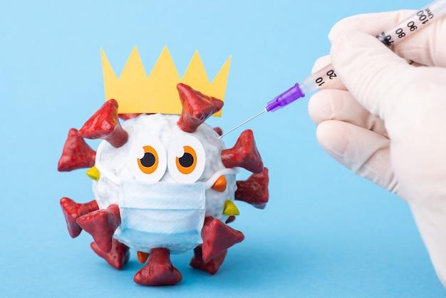 Mano con una siringa che fa l'iniezione a un virus covid-19 dei cartoni animati