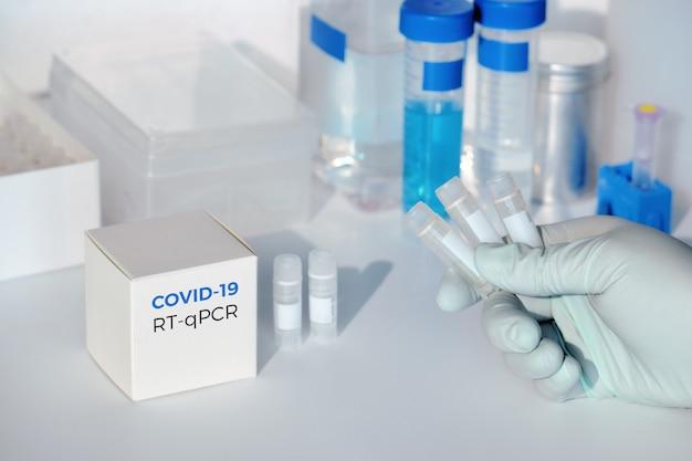 Mano con provette per il nuovo coronavirus covid-19 in campioni medici. il kit rt-pcr viene utilizzato per rendere il frammento di dna complementare all'rna del gene virale covid19 spike. test per la presenza di 2019-ncov.