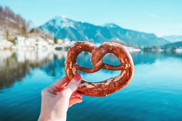Mano con pane tradizionale sullo sfondo del lago di montagna nelle alpi bavaresi, germania.