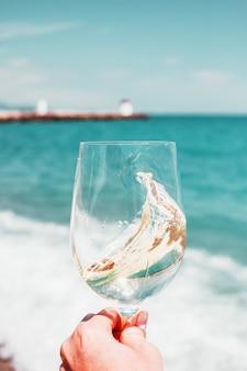 Mano con bicchiere di vino bianco su una spiaggia di onde di schiuma di mare turchese e sfondo di costa in francia