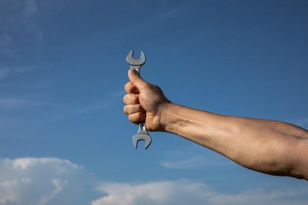 Mano con una chiave inglese su uno sfondo di un cielo blu scintillante.