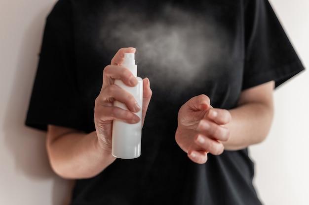 Mano di donna che applica spray alcolico o spray antibatterico per prevenire la diffusione di germi, batteri e virus. concetto di igiene personale.
