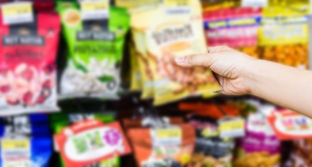 Mano della donna che sceglie o prendendo prodotti dolci, spuntini sugli scaffali in negozio