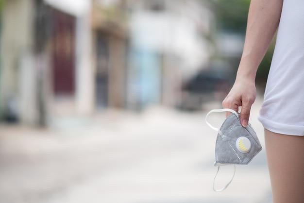Mano di donna tenuta maschera per prevenire la polvere pm 2.5 e il virus corona, covid 19
