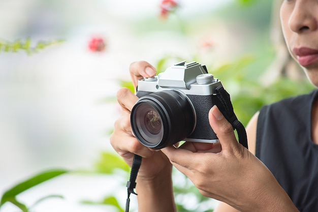 Mano donna che tiene la fotocamera scattare foto sfondo sfocato alberi.