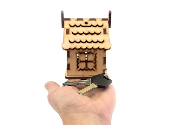 Mano di una donna che tiene piccola casa e chiavi. isolato su bianco, primo piano.