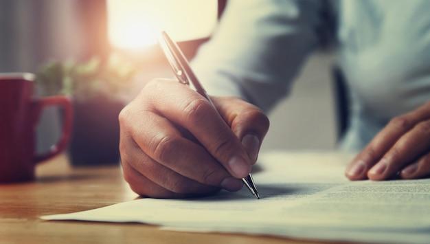 Mano della penna di holding della donna con scrittura sul rapporto di carta in ufficio
