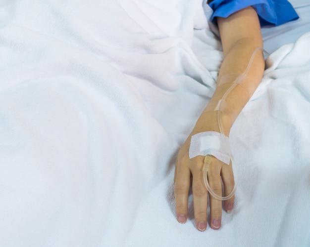 Mano del paziente della donna con soluzione fisiologica endovenosa, trattamento medico con la soluzione salina paziente, fine su