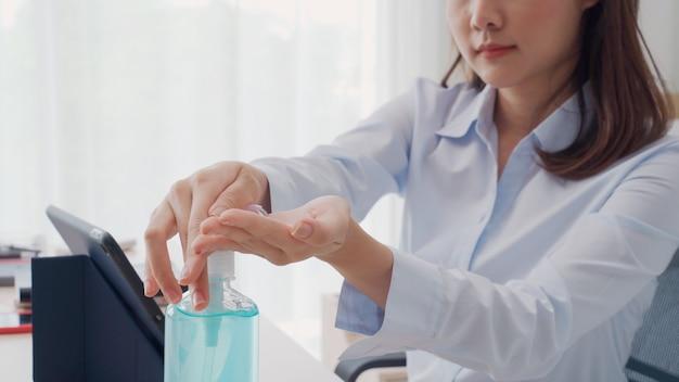 Mano della donna che preme il gel dell'alcool dalla bottiglia e che applica il gel disinfettante per il lavaggio delle mani per pulire e eliminare germi, batteri e virus. protezione pandemica, concetto igienico e sanitario.