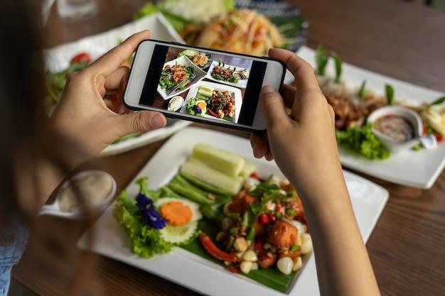La mano di una donna fotografa il cibo preparato da lei stessa. i venditori di cibo scattano foto con uno smartphone per pubblicarle sul sito web di ordinazione di cibo online.