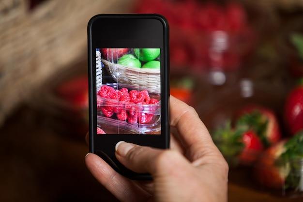 Mano di donna che cattura foto di frutti
