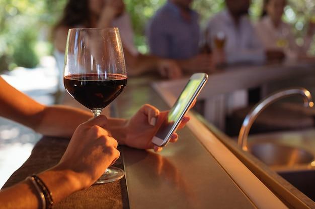 Mano di donna che utilizza il telefono cellulare pur avendo un bicchiere di vino