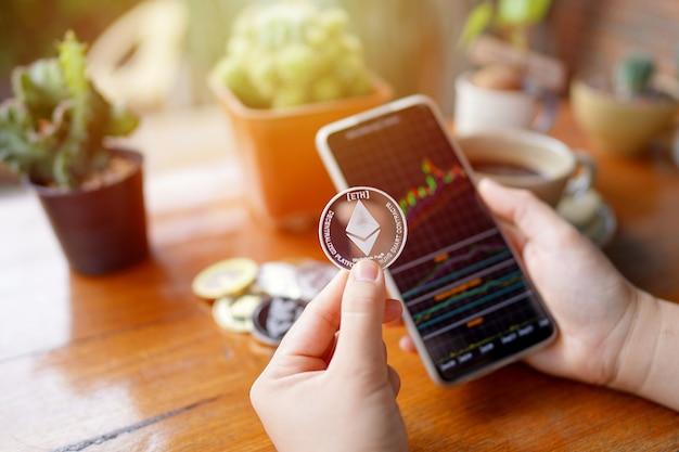Mano di una donna che tiene in mano una moneta ethereum e uno smartphone che mostra il grafico azionario nella caffetteria
