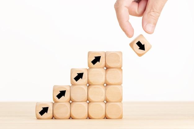 Mano e blocco di legno con freccia che cade. crollo del mercato azionario o concetto di crisi dell'economia finanziaria. concetto di incertezza aziendale e idea di rischio.
