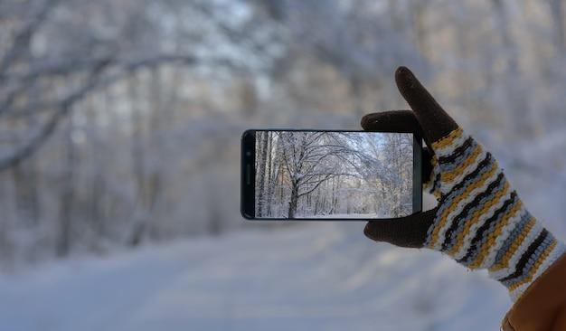 Mano in guanto di lana che tiene smartphone e scatta foto di un bellissimo paesaggio invernale