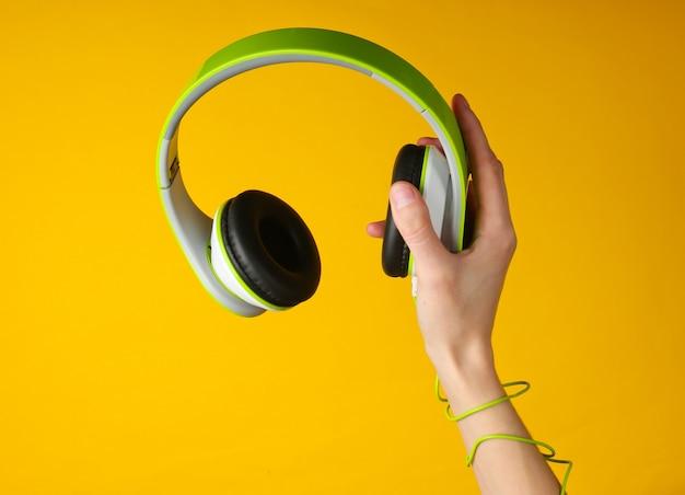 Il cavo avvolto a mano tiene le cuffie stereo su una superficie gialla