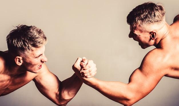 Lotta a mano, gareggia. mani o braccia dell'uomo. mano muscolare. due uomini a braccio di ferro. rivalità, primo piano del braccio di ferro maschile. uomini che misurano forze, armi.