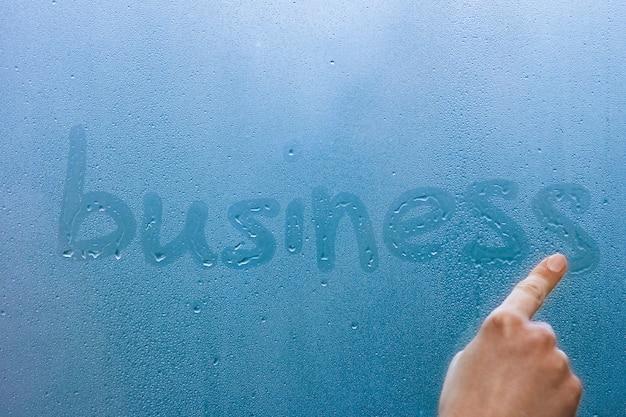 La mano scrive affari sul vetro della finestra con sfondo di gocce