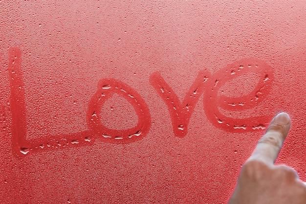 La mano scrive l'amore sul vetro della finestra con sfondo di gocce