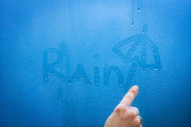 La mano scrive la pioggia sul vetro della finestra con sfondo di gocce