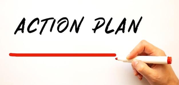 Mano che scrive piano d'azione con pennarello rosso. isolato su sfondo bianco. concetto di affari.