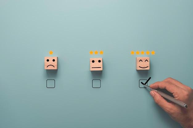 Segno di spunta di scrittura a mano per selezionare la faccia sorridente con cinque stelle su sfondo blu, concetto di valutazione del cliente.