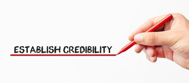 Scrittura della mano stabilisce la credibilità con l'indicatore rosso isolato su fondo bianco concetto di internet di tecnologia di affari stock image