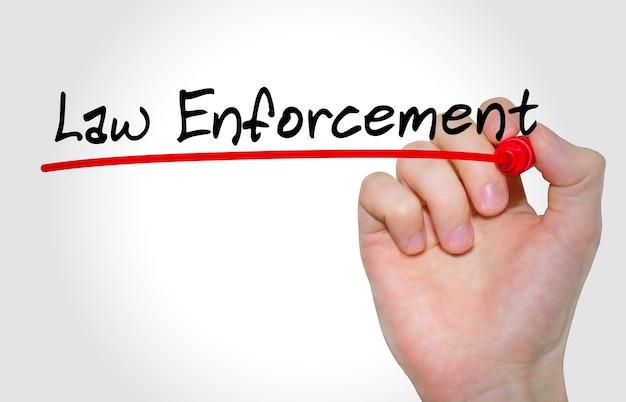 Mano che scrive iscrizione law enforcement con pennarello, concetto